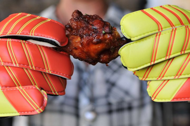 person holding chicken wing with keeper gloves